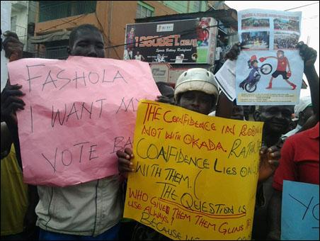 KADA RIDERS PROTEST BAN AND VICTIMISATION  - home made placard by okada operators - photo DSM