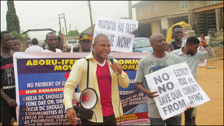 Femi Popoola, President of Akinola Youth, leading the protesters  round the streets in the community, photo DSM